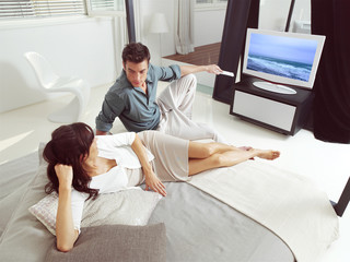 couple sitting on sofa and watching tv