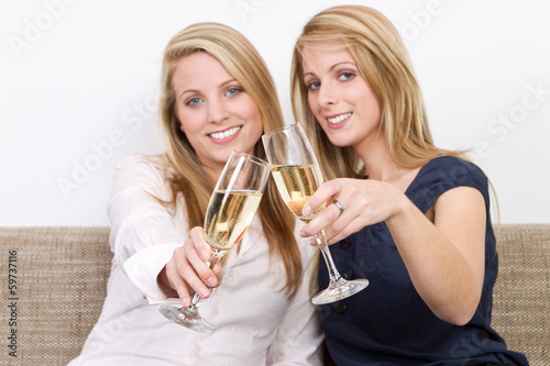 two women clink glasses