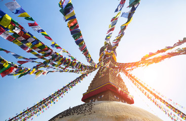 Prayer flags flying against the sun from the Boudhanath Stupa.