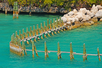 Old wooden pillars and rocks in the beautiful sea.