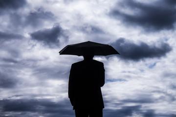 mann mit regenschirm und gewitterwolken
