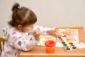 The little girl draws water color paints