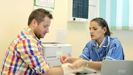 Doctor checking xray and talking with young man with broken hand