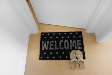 Welcome home on black mat