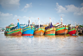 Colorful fishing boats berthed at the port in the Mekong Delta,