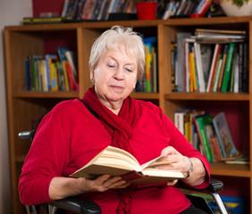 Seniorin im Rollstuhl liest ein Buch