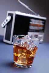 bicchiere di whisky con ghiaccio e apparecchio radio retrò