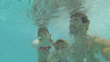 Dad with kids jumping in swimming pool