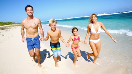 Family running on a paradisiacal beach