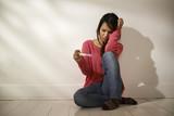 Sad Asian girl looking at pregnancy test sitting on floor