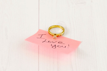 gold diamond ring with pink sticker on white wood