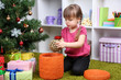 Little girl with Christmas ball near fir tree in room