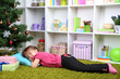 Little girl sleeping near Christmas tree in room