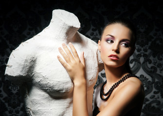 Attractive young lady with a statue on a retro background
