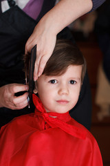 Young child with smile at the hairdresser having a haircut