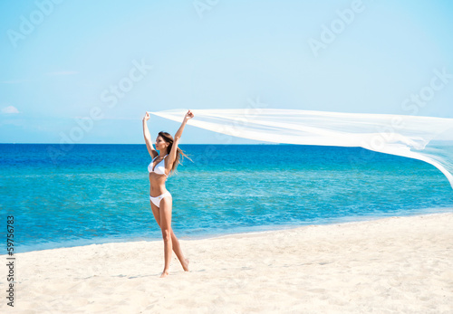A woman in a swimsuit posing with a silk blanket on the beach