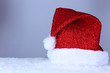 Santa hat on snow on grey background