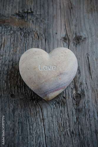 "Heart of stone with the inscription ""Love"" on an old wooden"