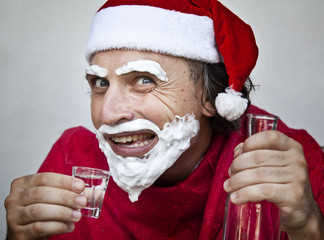 Bad Santa Claus with a beard of shaving cream drink vodka