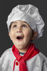 Funny, little boy preparing healthy food on kitchen over grey ba