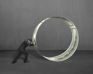Businessman pushing money circle in concrete background