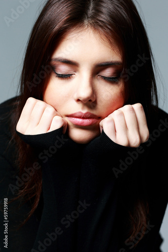Closeup portrait of a young pensive woman with closed eyes
