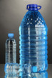 Different water bottles on grey background