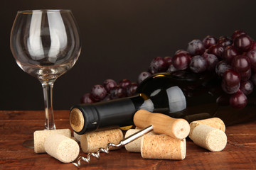 Wine and corks on wooden table on brown background