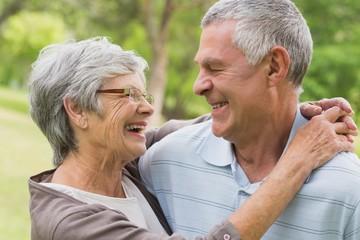 Happy senior woman embracing man at the park