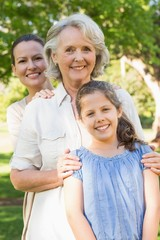 Smiling woman with grandmother and granddaughter at park