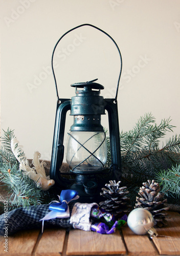 Kerosene lantern, pine cones and fir-tree branch
