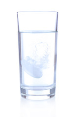 Glass with efervescent tablet in water with bubbles isolated