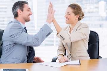 Smartly dressed colleagues giving high five in business meeting