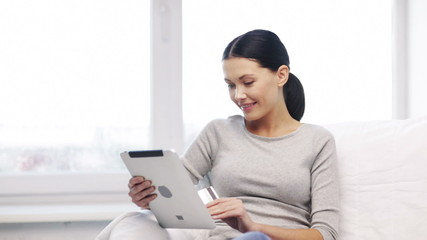 smiling woman with tablet pc and credit card