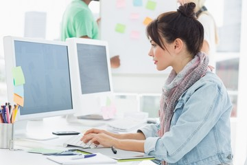 Artist using computer with colleagues behind at office