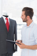Fashion designer with digital tablet looking at suit on dummy