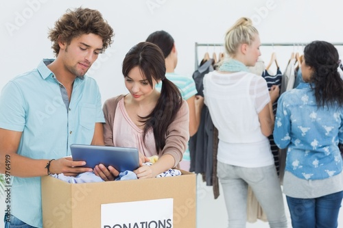 People with clothes donation while using digital tablet