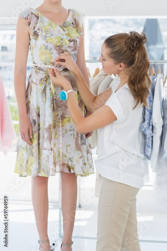Female fashion designer measuring model's waist