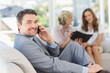 Businessman on call with female colleagues in background