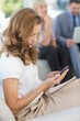Businesswoman text messaging with colleagues using laptop behind