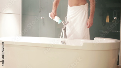 Man adding bubble bath gel to water in bathtub