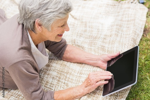 Smiling senior woman using digital tablet at park