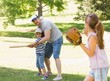 Family playing baseball in the park