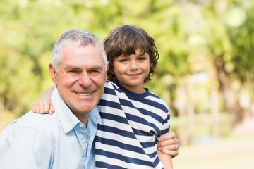 Grandfather and son smiling in park