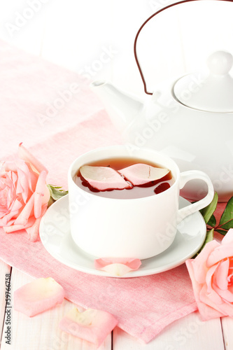 teapot and cup of tea with roses and on white wooden table
