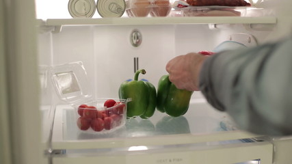 Male hand taking peppers, vegetables from the fridge