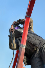 Construction site, worker welding metal tube
