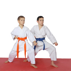 Athletes with a blue belt and orange belt stand in rack