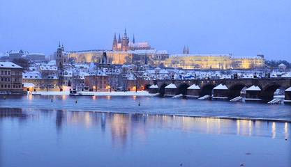 Evening colorful snowy Prague gothic Castle with Charles Bridge