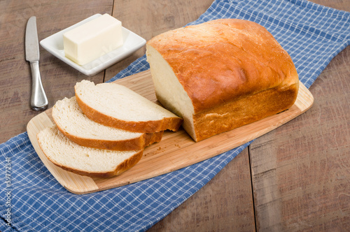 Loaf of sliced bread with butter plate